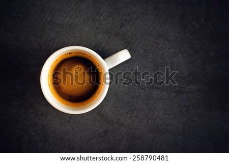 Top View of a Cup of Hot Black Coffee, White Ceramics Mug on Grunge Gray Table Cloth as Copy Space - stock photo