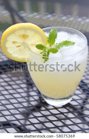 Top view of a cup of lemonade with a slice of lemon, sprig of mint and crushed ice.