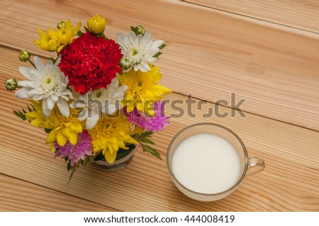 Top view of a cup of milk which decorate with flowers by wooden background - stock photo