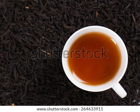 Top view of a cup of tea. Standing on tea leaves. - stock photo