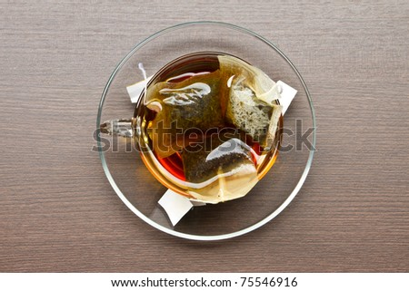 top view of a cup of tea with three tea bags on table