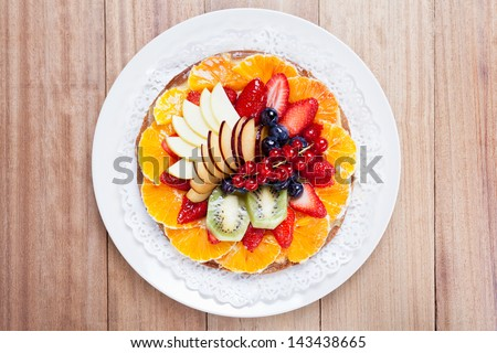 Top view of a delicious Fruit Tart placed in a dish on a wooden table - stock photo