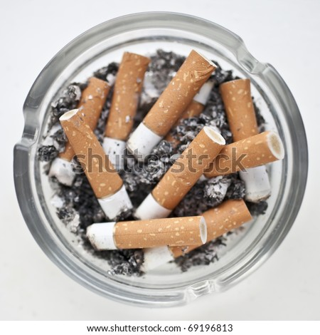 Top view of a dirty glass ashtray full  of stubbed out cigarette butts - stock photo