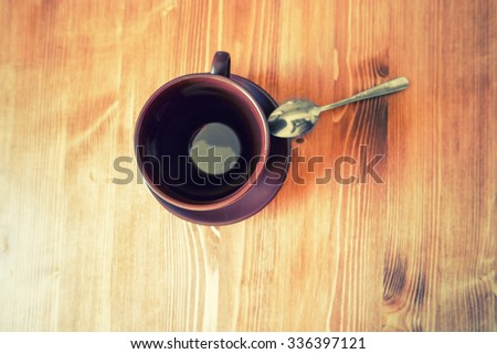 Top view of a empty brown cup of coffee on wooden table a lot of space for text. Close up overhead view of a empty cup of coffee on a rough textured wooden surface, with copyspace - stock photo