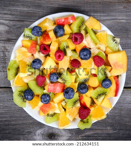 Top view of a fresh fruit salad with bananas kiwi orange blueberries and peach - stock photo