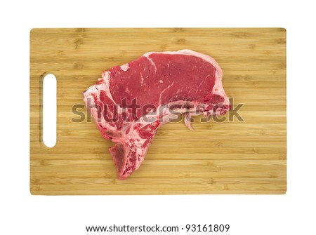 Top view of a fresh t-bone steak on a wood cutting board. - stock photo