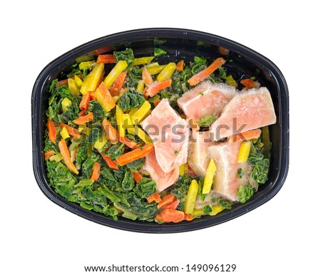 Top view of a frozen TV dinner of salmon, spinach, carrots and pasta on a white background.  - stock photo