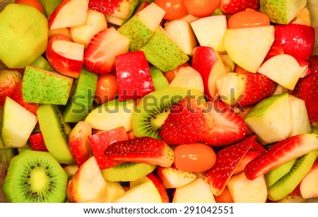 Top view of a fruit salad with strawberries, apple, kiwi for background