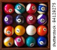 Top view of a full set of snooker balls inside an old wooden box - stock photo