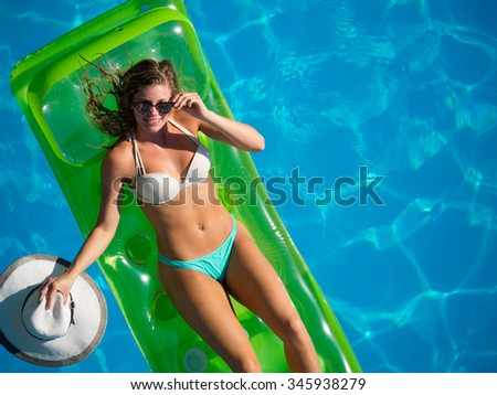 Top view of a  girl in the swimming pool on a lilo air matress - stock photo