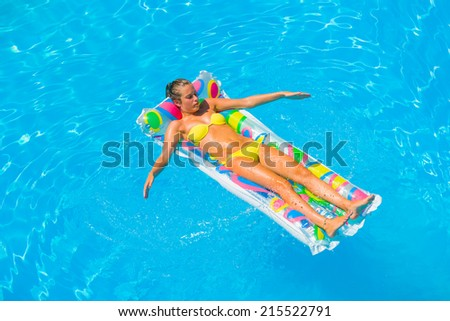 Top view of a  girl in the swimming pool relaxing on a lilo