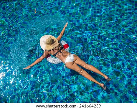 Top view of a  girl relaxing in the swimming pool - stock photo