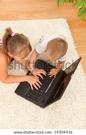 Top view of a girl typing on laptop while her brother is disturbing herself by touching the keys - stock photo