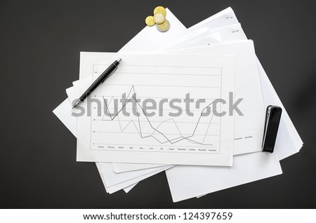 Top view of a graph document on a black office desk. - stock photo