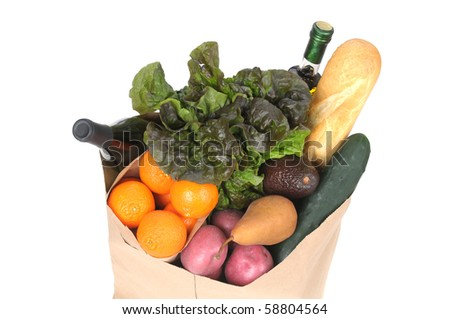 Top view of a grocery bag with fresh vegetables, fruit, wine and bread isolated on white.