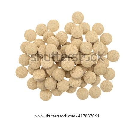 Top view of a group of brewer's yeast nutritional supplement tablets isolated on a white background.