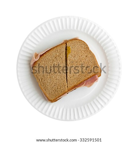 Top view of a ham and cheese sandwich that has been cut in half on a white paper plate atop a white background.