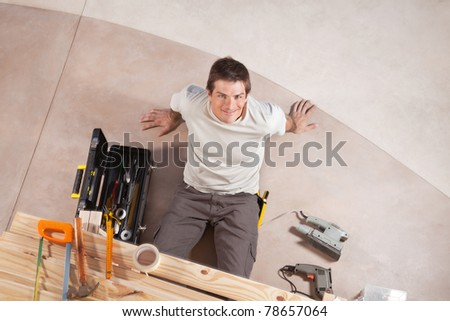 Top view of a happy handsome man with carpentry tools around - stock photo