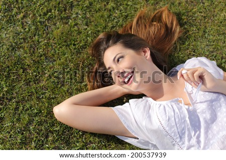 Top view of a happy relaxed woman lying on the green grass and looking at side smiling  - stock photo
