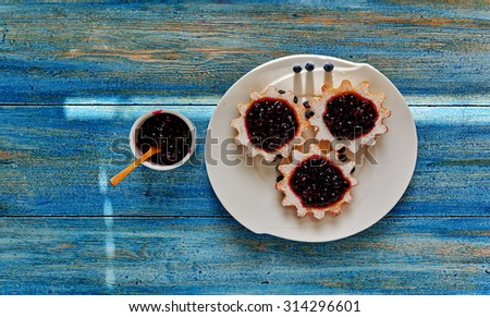 Top view of a housewife  prepared it served dessert, small tarts made from unleavened dough of shortcrust pastry with homemade jam from berries - stock photo