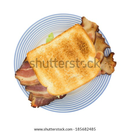 Top view of a large bacon sandwich with lettuce on an old blue striped plate. - stock photo
