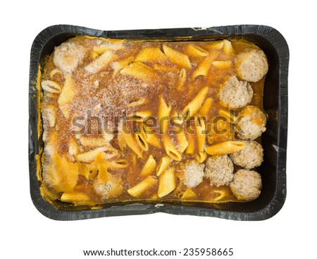 Top view of a large frozen TV dinner of penne pasta in a tomato sauce with meatballs in a black tray atop a white background.