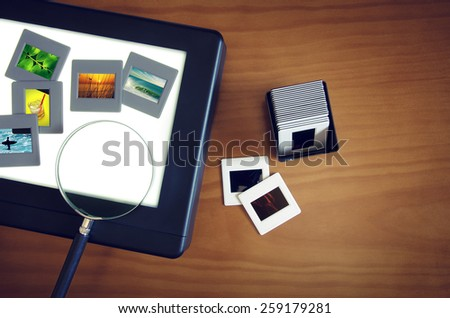Top view of a light-box with color slides and a magnifier lens over a wooden table - stock photo