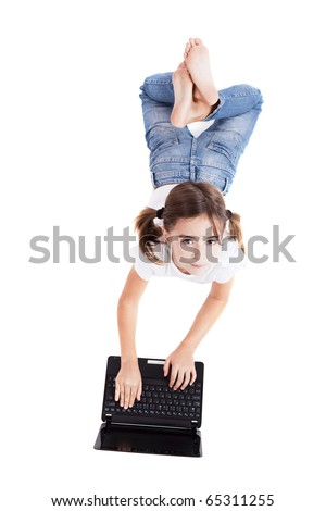 Top view of a little girl lying on floor working with a laptop - stock photo
