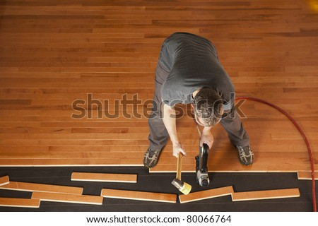 Top view of a man installing planks of hardwood floor - stock photo