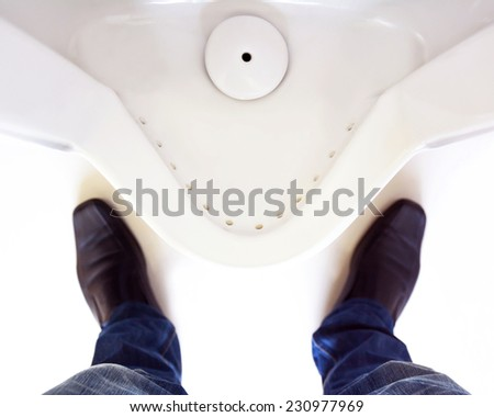 Top view of a man legs in front of urinal in men toilet - stock photo