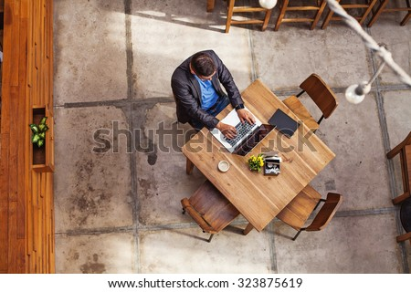 top view of a man working on his laptop in beautiful office interior - stock photo