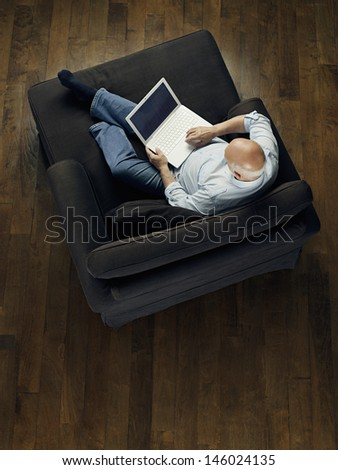 Top view of a mature bald man sitting on sofa and using laptop - stock photo