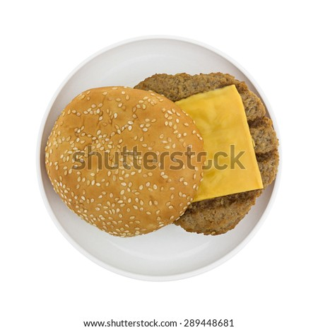 Top view of a microwaved cheeseburger with sesame seed bun on a small plate atop a white background. - stock photo