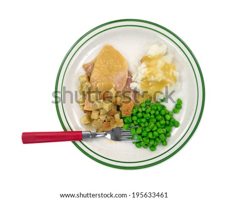 Top view of a microwaved sliced turkey in gravy with croutons, mashed potatoes and green peas on a plate with red handled fork. - stock photo