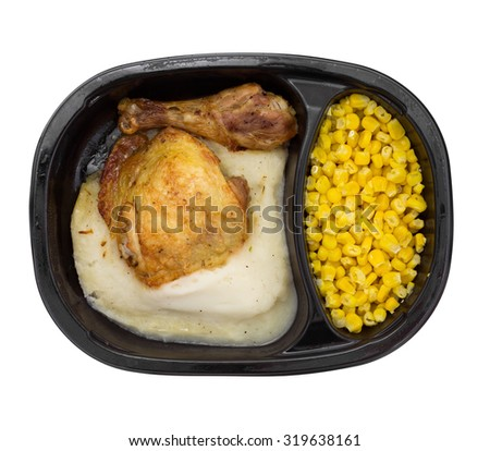 Top view of a microwaved TV dinner of roasted chicken with mashed potatoes and corn in a black plastic tray isolated on a white background. - stock photo