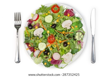 top view of a mixed salad plate, fork and knife  - stock photo