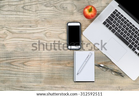 Top view of a organized, slightly fading, wooden desktop with apple for snack. Plenty of copy space.  - stock photo