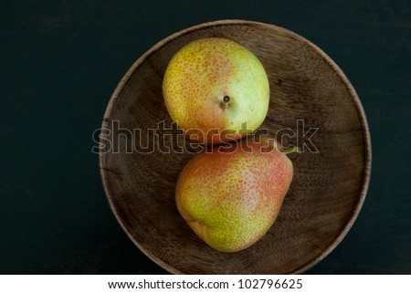 Top view of a pair of pears in a wooden bowl