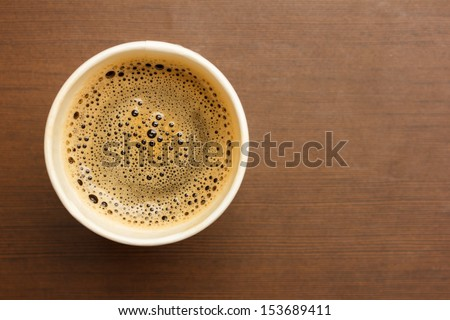 Top view of a paper cup of black coffee on wooden table - stock photo