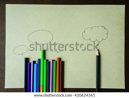 Top view of a pencil with a speech bubble isolated on brown paper background - stock photo