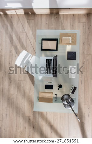 top view of a perfectly tidy glass desk with a laptop and a smartphone and other objects in the same color tone, sun casts graphics shadows  on the wooden floor - stock photo