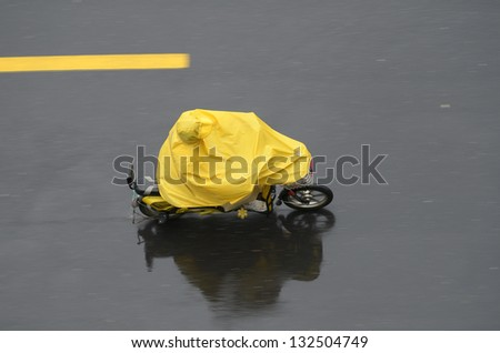 Top view of a person covered with yellow poncho riding mopped. Panning, motion blur. Hunagshan China. - stock photo