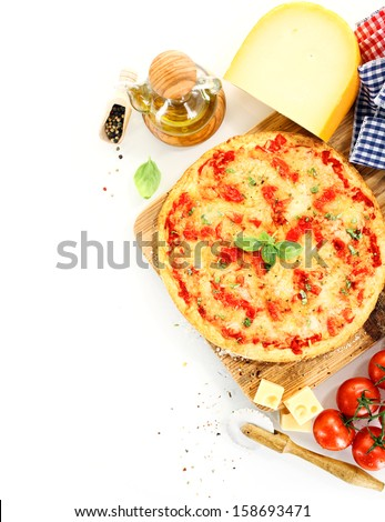 Top view of a pizza Margherita surrounded by ingredients like tomato, cheese, basil, olive oil and pepper and kitchen tools - stock photo