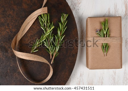 Top view of a plain brown paper wrapped present with rosemary and burlap ribbon.