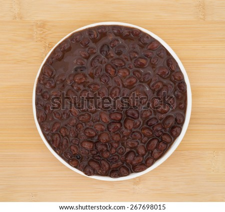 Top view of a plate of black beans in a chili sauce atop a wood table top. - stock photo