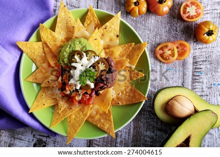 top view of a plate of homemade corn chips topped with vegetarian bean chili, mozarella, and jalapenos at wooden table - stock photo