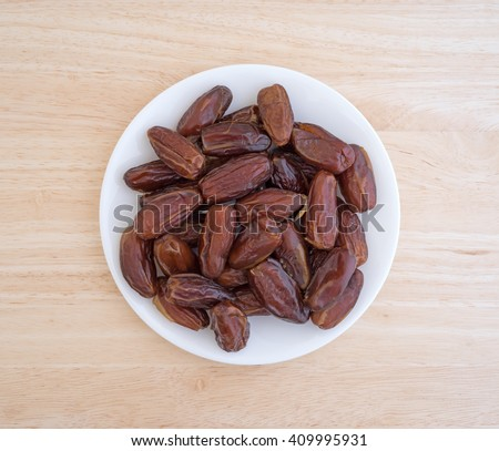 Top view of a plate of Tunisian pitted dates a wood table top. - stock photo