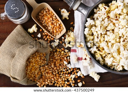 Top view of a pot full of freshly popped popcorn with salt and unpopped kernels on the side.  - stock photo
