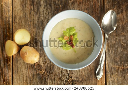 Top view of a potato soup in a blue bowl with fresh potatoes and spoon on a wooden background - stock photo