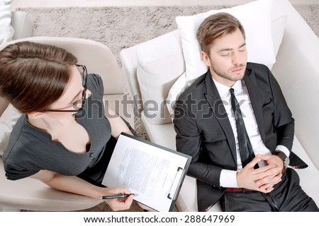 Top view of a psychologist sitting in the armchair holding a clipboard in her hands and looking at her client lying on a couch near relaxing ,thinking of his problems during therapy session - stock photo
